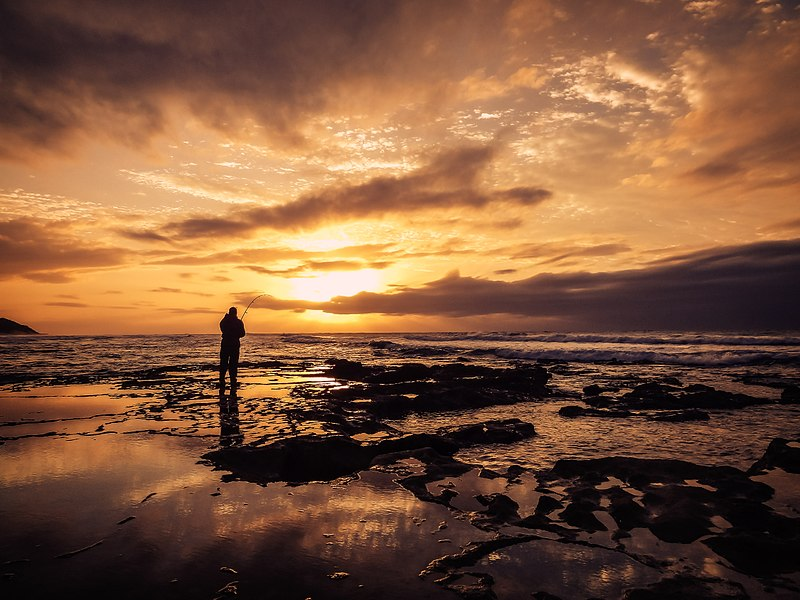 800px-Fisherman_fishing_at_sunset_(Unsplash) Ansteys Beach Bluff SA